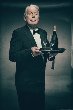 deportment: Portrait of Professional Looking Senior Male Butler Wearing Suit with Bow Tie and Carrying Tray with Bottle of Champagne and Two Glass Flutes Stock Photo