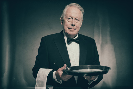 deportment: Portrait of Friendly Looking Senior Male Butler Wearing Formal Tuxedo Suit Carrying White Towel Over Arm and Empty Tray Stock Photo