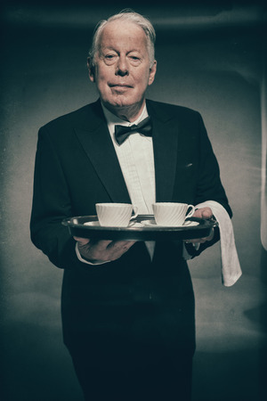 deportment: Friendly Looking Senior Male Butler Wearing Formal Tuxedo Suit with Bow Tie and Holding Tray of White Coffee Mugs or Tea Cups in Studio Stock Photo