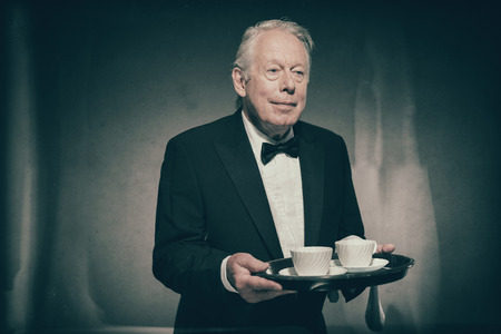 Waist Up Image of Smiling and Friendly Looking Senior Male Butler Wearing Formal Tuxedo Suit and Bow Tie and Holding Tray of White Coffee or Tea Cups, Looking to the Side with Copy Space