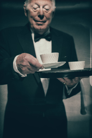 Senior Male Butler Dressed in Formal Tuxedo Suit Serving Coffee in White Mugs from Tray, Towards Camera as if from First Person Perspective