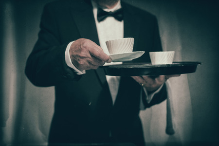 deportment: Close Up of Male Butler Wearing Formal Suit and Bow Tie Carrying Tray of White Coffee Mugs and Serving Cup Towards Camera