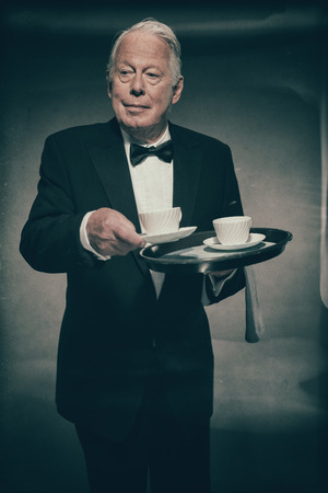 deportment: Friendly Looking Senior Male Butler Wearing Formal Suit and Bow Tie Carrying Tray of White Coffee Mugs and Serving Cup Towards Camera