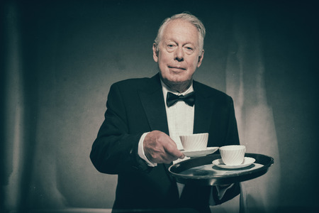 looking towards camera: Friendly Looking Senior Male Butler Wearing Formal Suit and Bow Tie Carrying Tray of White Coffee Mugs and Serving Cup Towards Camera