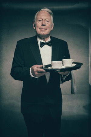 deportment: Friendly Smiling Senior Male Butler Wearing Formal Suit and Bow Tie Holding Tray with Two White Coffee Cups in Dimly Lit Studio