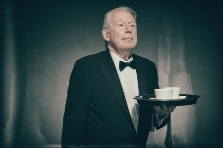 deportment: Refined Looking Senior Male Butler Wearing Formal Suit and Bow Tie Holding Tray with Two White Coffee Cups in Dimly Lit Studio with Copy Space