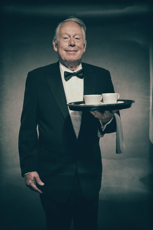 Friendly Smiling Senior Male Butler Wearing Formal Suit and Bow Tie Holding Tray with Two White Coffee Cups in Dimly Lit Studio
