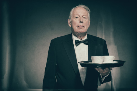 deportment: Waist Up of Senior Male Butler Wearing Formal Suit and Bow Tie Holding Tray with Two White Coffee Cups in Dimly Lit Studio