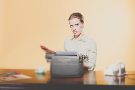 sexy secretary: Vintage 1950 secretaria joven que se sienta detrás de la lectura de periódicos escritorio. Mirando hacia la cámara.