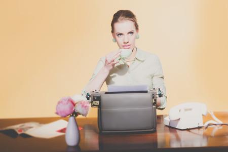 sexy secretary: 50s Retro joven mujer secretaria rubia sentado detrás de la taza de consumición mesa de té.
