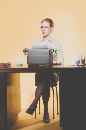 sexy secretary: Vintage Mujer 1950 secretaria joven detrás escritorio escribiendo en máquina de escribir.
