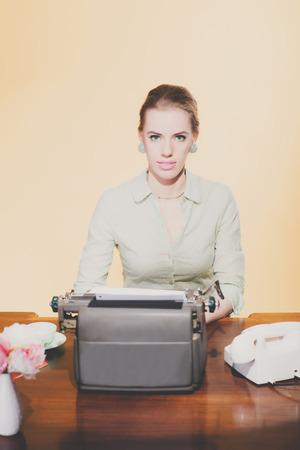 looking towards camera: Vintage 1950 blonde secretary woman sitting behind desk working on typewriter. Looking towards camera. High angle view.