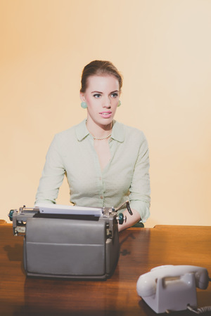 typewriter: Distracted retro 1950 blonde secretary woman sitting behind desk working on typewriter. High angle view.