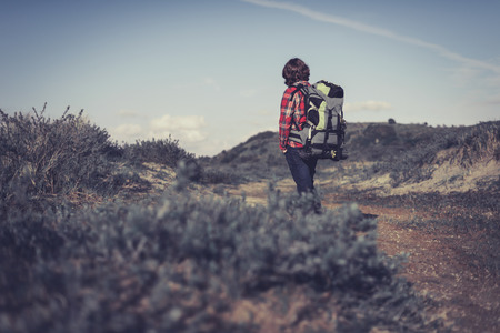 facing away: Backpacker wearing a large backpack of camping gear walking through hilly scrub standing facing away from the camera surveying his surroundings