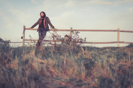 hilltop: Backpacker relaxing admiring the view standing leaning on a wooden rail fence on a hilltop in the distance, with copyspace Stock Photo