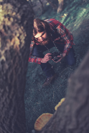 kneel down: Photographer taking a photo of a fungus growing on a tree in the wilderness kneeling down for a better angle and focus