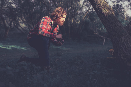 getting late: Rustic Outdoors Man Wearing Plaid Jacket Kneeling Outdoors with Camera Getting Ready to Photograph Large Yellow Mushroom Fungus at Base of Tree in Late Day Sunlight Stock Photo