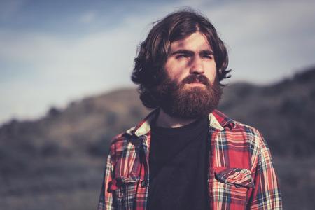 hombre con barba: Joven barbudo hermoso que se coloca mirando hacia el atardecer con una so�adora expresi�n pensativa, la cabeza y los hombros al aire libre en el campo Foto de archivo