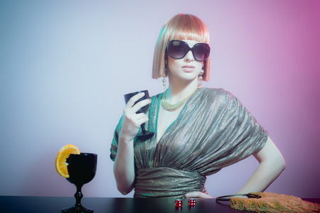 starlet: Glamorous and Sophisticated Female Starlet with Red Hair Wearing Sunglasses and Shiny Retro Gown Standing at Bar with Hand on Hip and Holding Wine Glass in Smoky Disco Night Club
