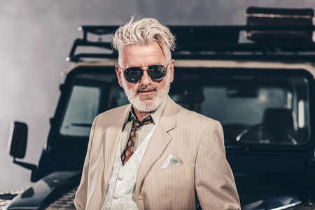 suit: Close up Elegant Senior Blond Guy Wearing Sunglasses, Looking at the Camera Against his Four-Wheel Vehicle.