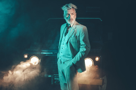 Elegant Middle Aged Man Posing in Formal Wear In Front of his Four-Wheel Vehicle and Looking Into Distance at Fuzzy Night