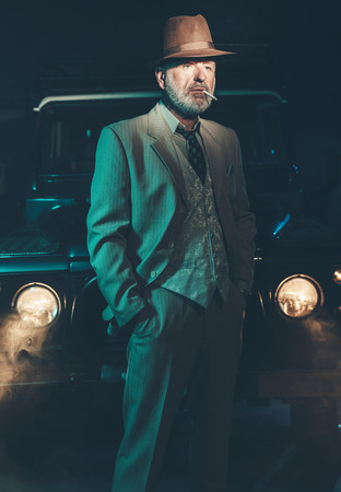 senior smoking: Serious Senior Bearded Businessman Standing While Smoking In Front of his Vintage Four-Wheel Vehicle at Night.