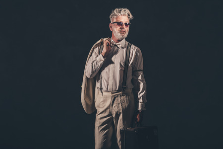 suave: Portrait of a Fashionable Matured Bearded Guy Holding his Coat and Suitcase Against Black Background