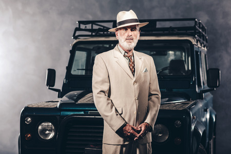natty: Elegant Senior Gentleman in Formal Wear with Hat, Standing Against his Vintage 4x4 Vehicle and Looking Into Distance. Stock Photo