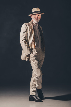 feet crossed: Stylish Adult Bearded Guy Wearing an Elegant Fashion, Standing with Feet Crossed and Looking at the Camera Against Black Background.