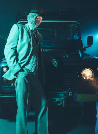 nonchalant: Elegant Middle Aged Man Leaning Against the Front of his 4x4 Vehicle with Pensive Facial Expression in the Middle of the Night. Stock Photo