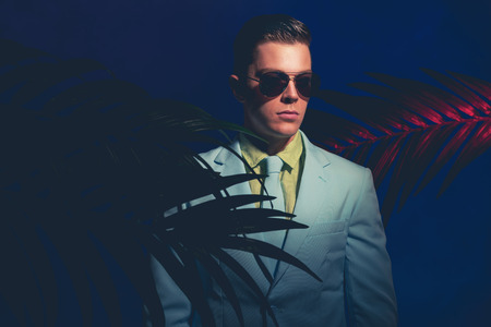 suave: Half Body Shot of an Elegant Young Man Wearing Sunglasses Standing Like a Mannequin between Palm Plants on a Dark Blue Gray Background.
