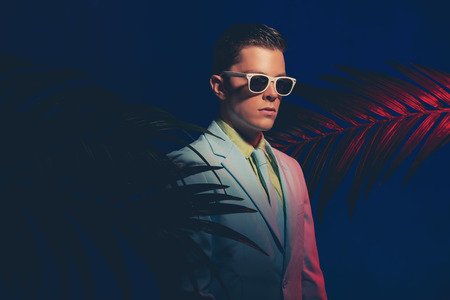 dapper: Close up Gorgeous Young Man Wearing Formal Suit with Sunglasses, Standing Between Plants Against Dark Blue Gray Background. Stock Photo