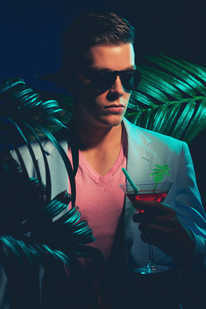 suave: Close up Gorgeous Young Man Wearing Formal Suit, Holding a Cocktail Drink While Standing Between Palm Leaves on a Dim Light.