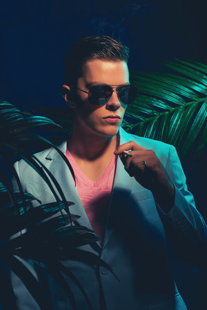 suave: Close up Handsome Young Man Wearing Formal Suit and Sunglasses, Standing Between Palm Leaves While Holding a Cigarette and Looking Into the Distance on a Dimmer Light. Stock Photo