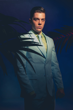 dapper: Handsome Man in Formal Wear Standing Between Palm Leaves Against Dark Blue Violet Background.