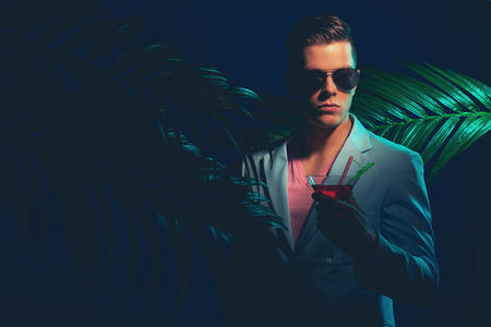 suave: Half Body Shot of an Elegant Young Guy with Sunglasses, Holding a Martini Glass with Drink Between Palm Plants Against Blue Background on a Dim Light. Stock Photo