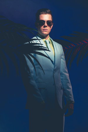 suave: Elegant Young Man Wearing Sunglasses Standing Like a Mannequin between Palm Plants on a Dark Blue Gray Background. Stock Photo