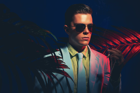 natty: Close up Elegant Young Guy Wearing Business Suit with Sunglasses, Holding a Cigarette Between Palm Leaves on a Dark Background. Stock Photo