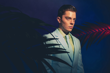 masculinity: Handsome Man in Formal Wear Standing Between Palm Leaves Against Dark Blue Violet Background.