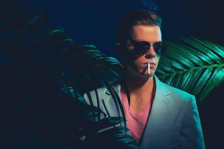 natty: Close up Elegant Young Man in Formal Wear, Posing Between Palm Plants While Smoking a Cigarette on a Dim Light.