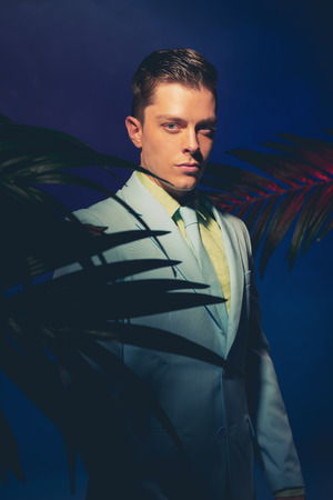 Half Body Shot of a Handsome Man in Formal Wear Standing Between Palm Leaves and Looking at the Camera Against Dark Blue Violet Background. Stock Photo