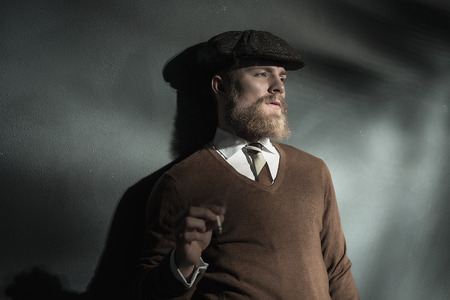cloth cap: Trendy man in a brown cloth cap leaning against a grey wall with his back to a beam of light smoking a cigarette, with copyspace