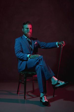 cane chair: Old-fashioned stylish bearded gentleman with a cane sitting in a chair in his three piece suit looking thoughtfully at the ca,era, darkness with atmospheric red lighting