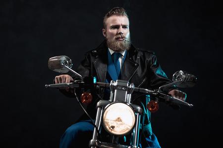 hombre fumando: Hombre de negocios machista con una barba que monta su moto en la oscuridad sentado esperando con el faro iluminado y un cigarrillo colgando de la boca mientras mira fijamente a la derecha de la trama
