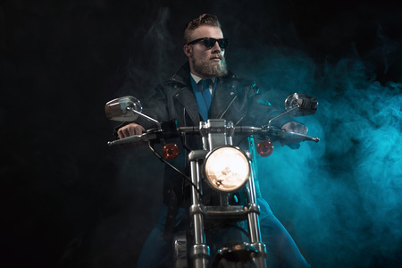 hombre sentado: Macho businessman in trendy sunglasses and a suit riding his motorbike in the darkness sitting waiting with the headlamp illuminated against a misty atmospheric shadowy background Foto de archivo