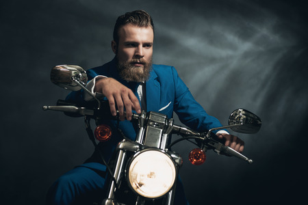 reverie: Handsome bearded businessman in a blue suit sitting waiting on a motorbike in the darkness looking thoughtfully, with copyspace Stock Photo