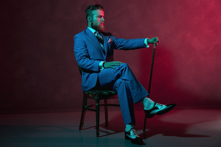 formal clothing: Elegant gentleman with a walking stick or cane sitting in a formal suit in a chair with atmospheric red lighting, side view Stock Photo