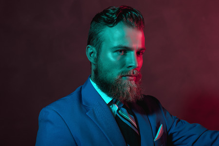 inscrutable: Stern bearded handsome man looking sideways at the with an inscrutable expression, head and shoulders in dark red lighting Stock Photo