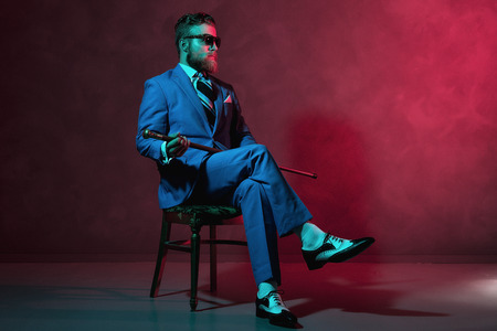 cane chair: Handsome trendy old-fashioned dandy with a beard and sunglasses sitting in a chair holding his cane, red toned lighting in darkness with copyspace Stock Photo