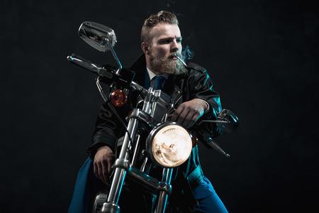 ヘッドランプの点灯を待って闇座っていると彼の視線、フレームの右側に、彼の口からぶら下がっているタバコで彼のバイクに乗って髭マッチョの実業家